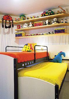 """As camas deslizantes correm em trilhos fixados em um painel na parede. De dia uma """"se esconde"""" sob a outra, liberando espaço para brincadeiras. À noite basta puxar uma delas. Na decoração, papel de parede listrado, cores vivas e iluminação atraente"""