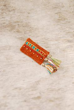 Rustic orange textile brooch with embroidery tassels and by Mioltu, €25.00