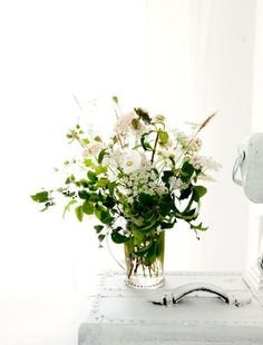French Country Rustic Shabby Chic Details: A vase of wildflowers stands on an old white trunk .