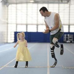 "This is five-year-old Ellie May Challis who lost her hands and lower legs to meningitis. She is the youngest person fitted with the same ""flex-foot"" prosthetics as Olympian Oscar Pistorius. Here he is giving her some pointers. Maybe we'll see her at the Games in 2024. Photo courtesy David Lux"