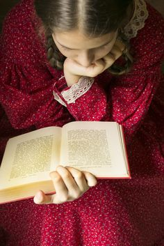 I think she is reading one of the Little House books, by Laura Ingalls Wilder. She is certainly dressed for it!