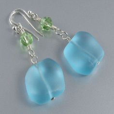 These pretty earrings are made with blue sea glass nuggets and green peridot Swarovski crystals. The earrings are approximately one and one half inches (3.81cm) in length, not including the sterling s