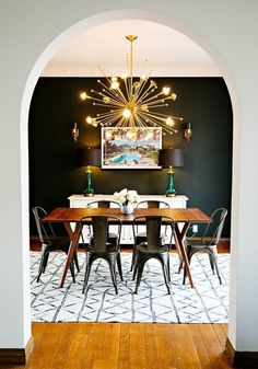 What I love about this space is the way that the black wall manages to still feel bright. Even with the dark wood and metal furniture the white buffet and rug and ceiling and the gold accents give it a light, airy feel...