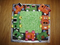 Moulded cake cars filled with sweets on cake road with desiccated coconut grass