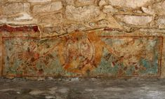 """At the base of the temple of Kukulcan at Mayapan is an area with interesting stucco work and murals.   Here you see a mural depicting two men with wooden poles holding up a circular banner, possibly a reference to the city's name, which means """"Banner of the Maya""""."""
