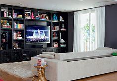Repleta de toy art, livros e outros objetos, a estante desenhada pela moradora, a designer de interiores Roberta, abriga a TV e outros equipamentos audiovisuais, armazenados nos compartimentos embaixo, com portas ripadas
