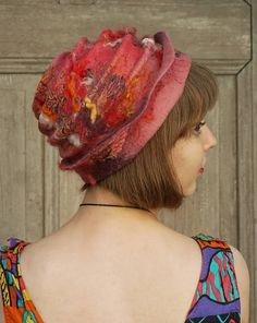 Beautiful fancy felted hat, hand shaped free style woman hat with little brim, one of a kind, in shades of dirty pink, orange and red, with pieces of decorative silk fabric, cotton lace , wool curls and bamboo fibers. Its made of merino wool using nuno felting technique with pieces of decorative fabric. Unique wearable art. Light, warm and elegant ! It may be the original addition to your outfit for any season!  Head circumference - ca 56 cm (22 inches)