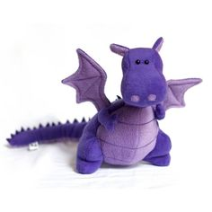 The Purple Yoki the Fat Dragon Kit is a Plush Animal Sewing Pattern & Fabric Kit from DIY Fluffies.  The recommended skill level for this kit is Advanced.  Kit includes soft fleece fabric in two colors, felt, embroidery thread, batting, eyes, pattern, and detailed instructions.  Your finished plush dragon will be approx. 10 inches tall.