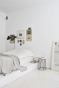 Simple and white bedroom with a minimalistic interior design and a metal bedside table.