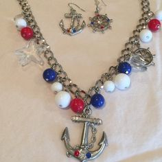 Set sail with this silver tone nautical set! Silvertone chain with red/white/blue beads and lucite charms. Jewelry Necklaces