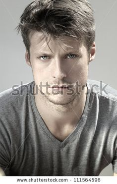 Highly detail portrait of young good looking man staring at viewer against neutral background - stock photo