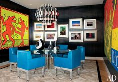 Art same time period. Mixing art photographs, gallery wall, Martin Lawrence Bullard, chrome based dining chairs, chairs that roll, mid century dining room, vintage chandelier, wood paneling, blue leather dining chairs