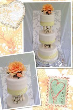 Ivory 3 tier wedding cake, triple layers in lemon drizzle with lemon curd & lemon curd buttercream filling. Ivory pillars & silk floral display