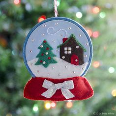 Introducing the Snow Globe Ornament, pattern in the Holiday Stitch-along Ornament Club! Members, check your email inboxes today! Create a miniature winter wonderland for your tree! The Snow Globe Ornament depicts a cozy cottage in the snow, framed by a Felt Christmas Decorations, Felt Christmas Ornaments, Christmas Crafts, Embroidered Christmas Ornaments, Christmas Patterns, Beaded Ornaments, Felt Ornaments Patterns, Felt Patterns, Globe Ornament