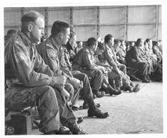 Briefing for D-Day of an American armored unit in England - Airborne troops = [Dans un hangar, réunion d'information sur le D-Day pour les soldats des troupes aéroportées].