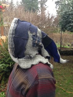Upcycled Patchwork Hood Hat perfect for Renaissance Fairs or Festival Wear. Shades of Blue, Black and Grey. 24 inches long. Suitable for men or women. This patchwork hood is made from several different recycled wool sweaters. Serged threads are in black. It can be tied and worn as a collar or on your head as shown. This one has longer get ties than others. It is unlined.    Hand wash or gentle machine cycle/ lay flat to dry.    By recycling responsibly, people and the planet benefit in e...