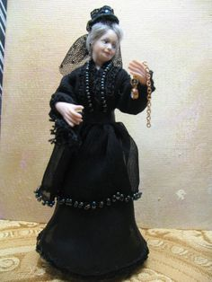 A Miniature 1/12 scale porcelain doll depicting a Victorian widow.  By KaysStudio on Etsy, made by Kay Brooke.