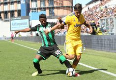 Paulo Dybala (R) of Juventus competes for the ball with Claude Adjapong (L) of US Sassuolo Calcio during the Serie A match between US Sassuolo and Juventus at Mapei Stadium - Citta' del Tricolore on September 17, 2017 in Reggio nell'Emilia, Italy.