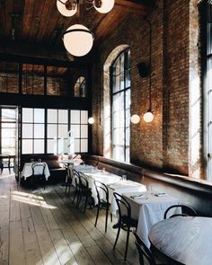 brick dining room at the wythe hote locatedl in williamsburg, brooklyn. #brooklynhotel #williamsburghotel #hotel #boutiquehotel #williamsburg #brooklyn #restaurantinterior #brickwalls #exposedbrick #bentwooddiningchairs #globelighting #lightingfixtures #modernlighting #steelwindows