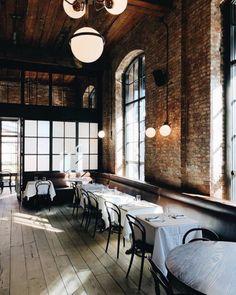 brick dining room at the wythe hote locatedl in williamsburg, brooklyn. #brooklynhotel #williamsburghotel #hotel #boutiquehotel #williamsburg #brooklyn #restaurantinterior #brickwalls #exposedbrick #bentwooddiningchairs #globelighting #lightingfixtures #modernlighting #steelwindows