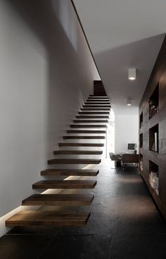 floating stairs rise to loft-like area, no rails, can really imagine windows and sliding door on the blank wall... note niche openings in facing wall