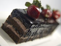 piece of black forest cake topped with strawberry on white plate by NareshKumar19