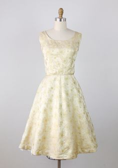 1960s vintage party dress in metallic gold brocade with a light green tint. Brocade fabric is embroidered with flowers and vines with metallic gold