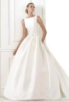Brides: Pronovias. Low-waisted princess style dress in mikado silk. Bateau neckline with edging. Bow at the waist with a belt effect.