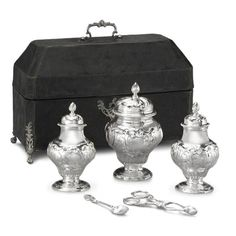 Tea Equipage by John Derussat, c.1750. A mid-eighteenth century pair of tea caddies, sugar box and set of twelve teaspoons, and pair of sugar nippers all fitting into a contemporary black lackuered box. The teaspoons are formed as Rococo Grand pattern, and a pair of sugar tongs is matched design. Maker's mark on teaspoons, a pair of sugar tongs script JD, acorn above.