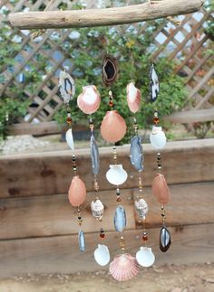 This is an agate beauty perfect for any patio, garden or home. The chimes hang from natural sea-worn driftwood collected from beaches in the Pacific Northwest. It features eight beautiful natural geo agate slabs. Agates are considered a semi-precious gemstone. A stone of strength, the agates most noticeable properties over all are balancing yin/yang energy, courage, healing and calming. Several different types of shells make up this beautiful mobile including Mexican flat shells, scallop...
