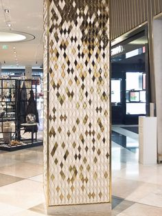 """A specially designed diamond with an angled face was arrayed to convey falling golden gradients of colour in the studio's third installation for the Dubai Mall. The columns are composed of ceramic tiles in both matt white and high gloss gold finish, angled in varying directions to show reflect shimmering light in the surface"""" From…"""