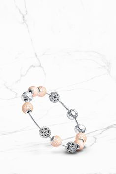 Slender sterling silver PANDORA ESSENCE COLLECTION bracelet styled with Appreciation, Love and Joy charms. The silver and soft pink charms make it feminine and stylish. #PANDORAessencecollection