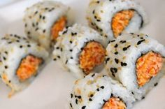 SPICY CRAB SUSHI ROLL RECIPE ==  Ingre­di­ents==  Sushi Rice (pre­pared, one large handful), Nori Sheet (1/2), Toasted Sesame Seeds, Black Sesame Seeds, Spicy Crab (srirachi hot sauce, shred­ded imi­ta­tion crab sticks, masago, mayonnaise) ====