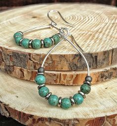 "Silver plated hoops with small green turquoise magnesite stones, separated by hand forged silver beads. Ear hook is sterling silver. Approx. 2"" in length."