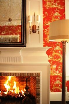 Ron van Empel of Empel Collections' home showroom with Red chinoiserie toile wallpaper around a white fireplace