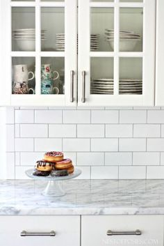 Remodeling Kitchen Countertops Tips on installing white subway tile. - Our all white kitchen gets subway tile backsplash installation the DIY way. Ideas and tips on subway tile backsplash installation for your own home. Backsplash Herringbone, White Subway Tile Backsplash, Grey Subway Tiles, Subway Tile Kitchen, Backsplash Ideas, Backsplash Design, Tile Kitchen Countertops, White Tile Backsplash Kitchen, Kitchen Cabinets