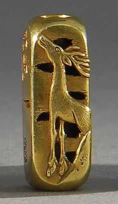 Lot 95: GOLD OJIME In rectangular form with relief and engraved design of a deer in a landscape. Signed in gourd-form cartouche. Length 19mm... - Eldred's | Invaluable