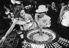 Jake Freedman, owner of Sands Hotel, sporting fancy cowboy outfit at roulette table w. showgirl at his establishment.  Location:Las Vegas, NV, US  Date taken:June 1955