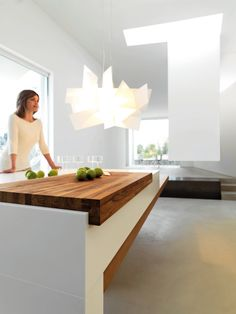 Modern kitchen island design with integrated butcher block. Kube with elm wood doors and stainless steel worktop. Island version with Corian worktop and Iroko Wood chopping boards.