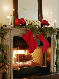 Red and white poinsettia flowers above fresh green garland bring in our favorite Christmas hues. Candles and a crackling fire create a cozy and inviting living room.