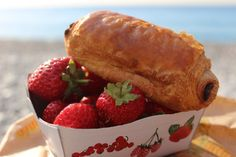 Nice, France: Breakfast of Pain au chocolate and fresh strawberries on the beach.