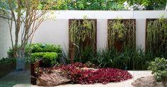 O paisagista Odilon Claro, da Anni Verdi, construiu este jardim de inverno dentro do banheiro de uma suíte. Na parede está o jardim vertical, montado com quadros de aço corten e placas de ripsális. Plantas do tipo lambri rodeiam a fonte central. À esquerda do jardim está uma grande jabuticabeira híbrida. Para forrar o chão da área, pedriscos