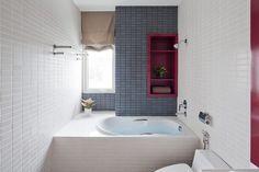 Kleines Bad mit Badewanne und roten Farbakzenten