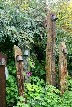Rustic lighting on stone pillars in the garden....old galvanized buckets turned upside down to house the light fixture
