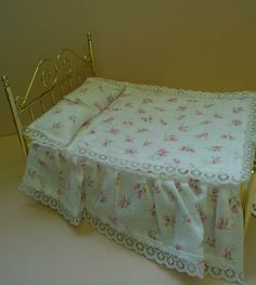 1/12 scale. Handmade bedding set in pretty roses print; comprises of valence, quilt and 2 pillows.  www.colnedollhouseshop.co.uk