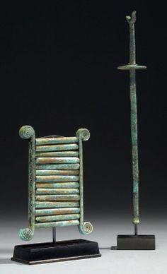 CHALCOPHON formé de deux tiges latérales aux extrémités spiralées maintenant quatorze tubes. Il est accompagné d'une MAILLOCHE dont l'extrémité est en forme d'oiseau. (2 objets). Bronze. Phénicie, VIIIe-VIIe siècles av. J.-C. H_14 cm (chalcophon) et 30 cm (mailloche) Ancienne collection européenne, avant 1990. Bibliographie: U. Gehrig & G. Niemeyer, Die Phönizier im Zeltalter Homers, Hanovre, 1990, p. 182, n° 128.