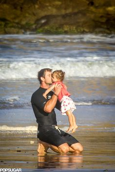 Chris Hemsworth kissing his daughter during a family beach day.