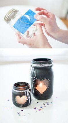 Porta velas de frascos de vidrio, pintados en negro y con una ventana en forma de corazón que deja ver el interior. Decorados con cuerda de algodón en el gollete de los frascos.