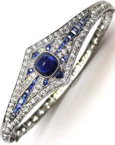 Belle Epoque cabochon sapphire and diamond hinged bangle, probably American c.1900, millegrain set with a sugar loaf sapphire to center, framed by a lozenge of radiating  cut sapphires and brilliant cut diamonds.