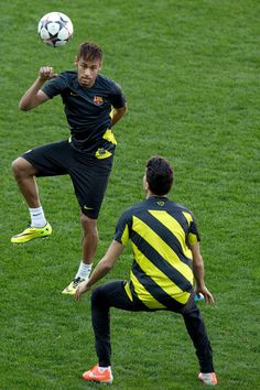 Neymar JR. (L) controls the ball with team-mate Marc Bartra (R) during a training session the day before the UEFA Champions League Quarter-final match between Atletico de Madrid and FC Barcelona at Vicente Calderon Stadium on April 8, 2014 in Madrid, Spain.